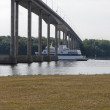 Foto Stock: Ferry Passing Underneath Bridge
