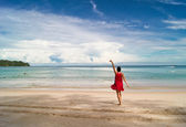 Girl in red is dancing on the beach — Stock Photo