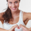 Stock Photo: Young woman doing a heart with hands