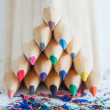 Triangular pile of colored wooden pencils — Stock Photo