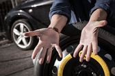 Driver showing his dirty hands changing car tyre — Stock Photo