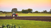 Tractor and plow in field — Stockfoto