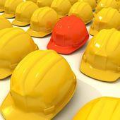 Red helmet between series of yellow helmets. — Stock Photo