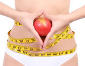 Woman's waist with measuring tape holding red apple — Stockfoto