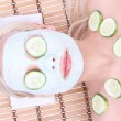 Young girl with facial mask of cucumber on bamboo mat , spa — ストック写真 #13820203