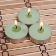 Stockfoto: Three burning candles on bamboo mat