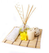 Spa setting with aroma sticks, candle, towel and flower on bamboo mat isolated on white — Stok fotoğraf