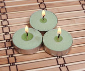 Three burning candles on bamboo mat — Стоковое фото