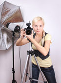 Professional photographer, young beautiful girl with the camera in photo studio — Stock Photo