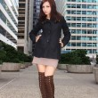Brunette girl in sexy boots posing in the city — Stock Photo