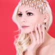 Very beautiful blonde girl with pearl accessories on her head on red background — Stock Photo #16330249