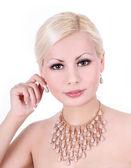 Mooie jonge vrouw met parel ketting en oorbellen op witte achtergrond — Stockfoto