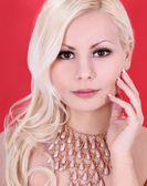 Very beautiful blonde girl with pearl necklace on red background, closeup — Stock Photo