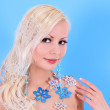 Blonde young woman decorated with snowflakes over blue background — Stock Photo