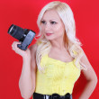 Beautiful photographer with the professional camera over red background — Stock Photo #16848039