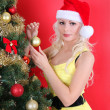 Blonde girl in Santa hat decorating Christmas tree over red background — Stock Photo #16848191
