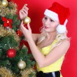 fille blonde en bonnet de décorer le sapin de Noël sur fond rouge — Photo