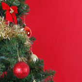 Christmas balls on Christmas tree branch, over red background — Zdjęcie stockowe