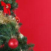 Palle di natale sul ramo di un albero di natale, su sfondo rosso — Foto Stock