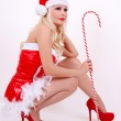 Beautiful sexy Santa girl with candy cane, sitting on white background — Stock Photo