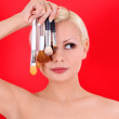 Beautiful blonde young woman with makeup brushes over red background — Stock Photo