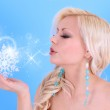 Blonde young woman blowing kiss with snowflakes and stars on blue background — Stock Photo #17606433