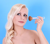 Beautiful blonde young woman with makeup brush over blue background — Stock Photo