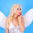 Beautiful blonde angel girl over blue background — Stock Photo