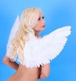 Beautiful blonde angel girl over blue background, back — Stock Photo