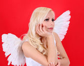 Beautiful blonde angel girl over red background — Stock Photo