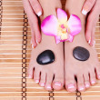 Stock Photo: Foot care, beautiful female feet and hands with french manicure on bamboo mat with orchid flower and spstones