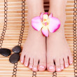 Beautiful manicured female bare feet with orchid flowers and spa stones over bamboo mat, pedicure, foot care — Stock Photo