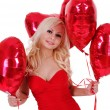 Beautiful blonde young woman in red dress smiling and holding red heart shaped balloons for Valentines day isolated on white background — Stockfoto
