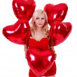 Stock Photo: Beautiful blonde young woman in red dress smiling and holding red heart shaped balloons for Valentines day isolated on white background