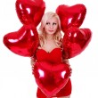 Beautiful blonde young woman in red dress smiling and holding red heart shaped balloons for Valentines day isolated on white background — ストック写真 #19447107