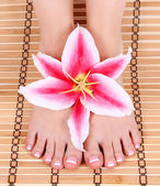 Beautiful manicured female bare feet with pink lily flower over bamboo mat feet care, spa — Stock Photo