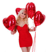 Beautiful blonde young woman in red dress smiling and holding red heart shaped balloons for Valentines day isolated on white background — Stock Photo