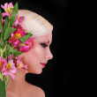 Beautiful blonde young woman with pink irises flowers over black background, fashion model — Stock Photo