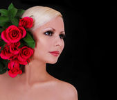Beautiful blonde young woman with red roses over black background, fashion portrait — Stock Photo