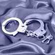 Handcuffs and keys on silk fabric — Stock Photo