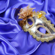 Gold carnival mask on blue silk fabric — Stock Photo #21381409