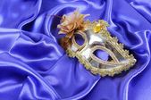 Gold carnival mask on blue silk fabric — Stock Photo
