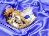 Gold carnival masks on blue silk fabric — Stock Photo