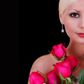 Beautiful young woman with red roses over black background with copy space, fashion portrait — Stock Photo