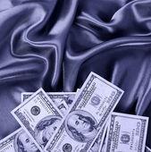 Dollars bills on silk fabric, sexy money — Stock Photo
