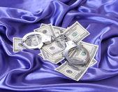 Money and handcuffs on blue silk fabric, dollars bills — Stock Photo