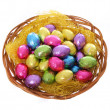 Colorful chocolate easter eggs in basket isolated on white background — Stock Photo
