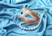 Glitter gold mask and pearl necklace on turquoise silk drape background — Stock Photo