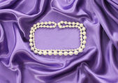 Pearl necklace on blue silk drape, background with copy space — Stock Photo