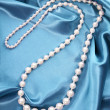 Pearl necklace on turquoise silk fabric, luxury — Stock Photo